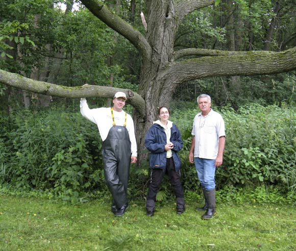 Photo of Caroline Tanguay with specialists, in front of a butternut's trunk