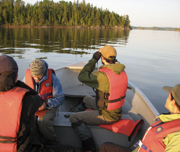 Photo of four students in a boat on a lake, looking out at their study site